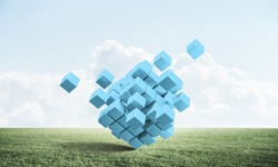 Abstract blue cubes on green meadow. Digital technology and innovation solutions. New approach to business management. Nature landscape with green grass and blue sky. Mixed media with 3D object