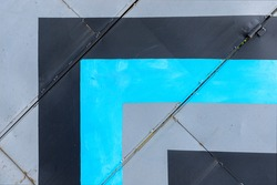Abstract blue, grey and black angled lines on old metal wall, geometric shapes, vivid colors in architecture.