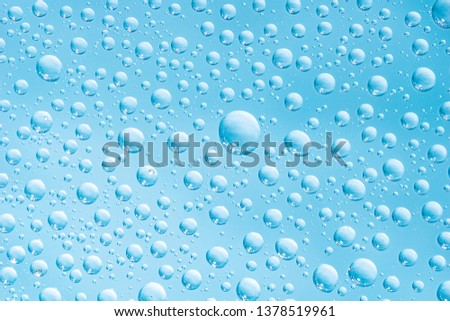 Abstract blue water drops on glass surface look like bubbles in water macro picture