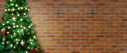 Abstract blur decorated Christmas tree with baubles on brick wall background