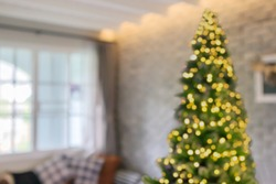 Abstract blur decorated Christmas tree with bokeh light in living room interior background