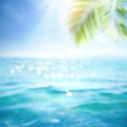 Abstract blur defocused background, toned blue, nature of tropical summer with rays of sun light. Beautiful sun glare on sea water and palm leaves against sky. Copy space, summer vacation concept
