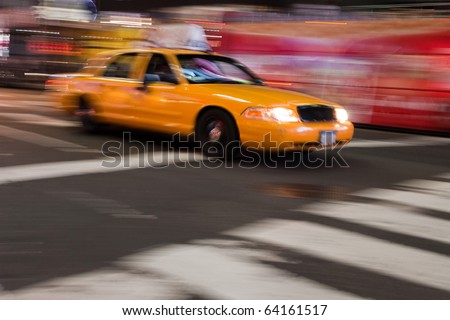 Abstract blur of a night time urban street scene with a yellow taxi cab speeding by.  Slow shutter speed panning technique used for motion blur.