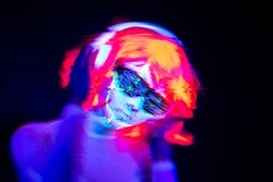 Abstract blur of beautiful sexy woman with cyborg UV face paint, wig, glowing glasses, glowing clothing and headphones in front of camera, Half body shot. Asian woman. Party concept.