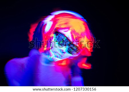 Abstract blur of beautiful sexy woman with cyborg UV face paint, wig, glowing glasses, glowing clothing and headphones in front of camera, Half body shot. Asian woman. Party concept. #1207330156