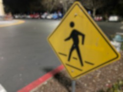 Abstract blur of diamond shaped pedestrian crossing sign.