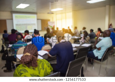 Abstract blur of people or participant are training in the lecture room with lecturer presented the presentation by a projector and a screen of the projector