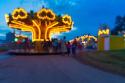 Abstract Blur or Defocus Background image of People, Male Female and Kids, Walking around in Local Amusement Fun Park or Fun Fair in Thailand at Twilight.