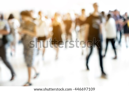 Stock Photo Abstract blur people walking in fashion mall. Sunlight shining through window in summer