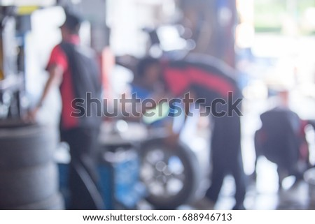 Abstract blur section of technician repairing the car to change at wheel in garage. #688946713