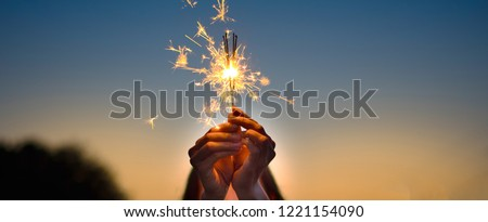 Abstract blur sparklers for celebration background,Motion by wind blurred woman hand holding burning Christmas sparkle on nature and twillight sky background.Winter vintage film grain filter style. #1221154090