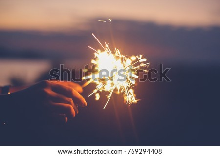 Abstract blur sparklers for celebration background,woman hand holding a burning sparkler light with purple sky background.closeup in female hand in dark. happy holidays.Vintage flim grain Style. #769294408