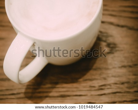abstract blur : white coffee cup with hot cappuccino coffee inside put on wooden table background #1019484547