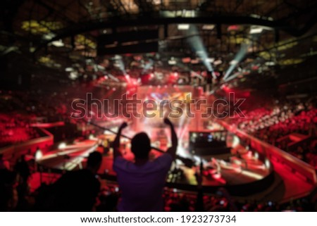 Abstract blurred background of big esports gaming event at big arena. Man with a hands raised. Stock fotó ©