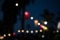 Abstract blurred background of colorful glowing night festive light bokeh in twilight time at the beach with blue sky and coconut palm tree, can be used for summer night party background