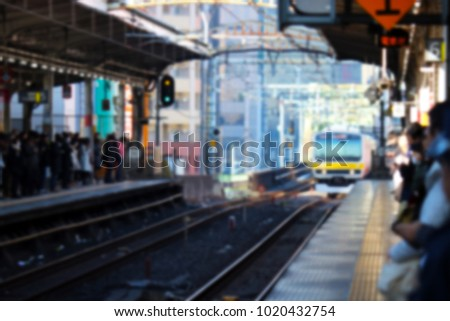 Abstract blurred background of JR Chuo line yellow train that running to the station platform while crowd of people are waiting it. Rush hour in Japan blurred image concept. #1020432754