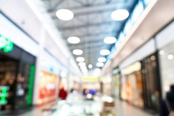 Abstract blurred background of modern luxury department store hall or shopping center mall. Blurred lights background. Blurred defocused bokeh lights with modern white interior architecture