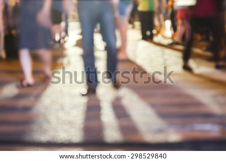 abstract blurred background of people standing on concrete ground while watching concert with shadows from the concert and a night light in the city, can use for background or your decoration. - Shutterstock ID 298529840
