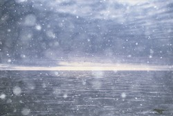 abstract blurred background, snow falls on the sea, northern cold sea, climate winter view