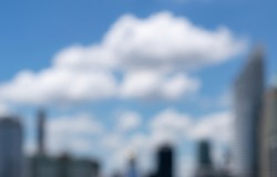 Abstract blurred blue sky and clouds background in city. Defocused tall skyscraper buildings in daytime with big white clouds. Copy space for texting and designing in real estate and urban concept