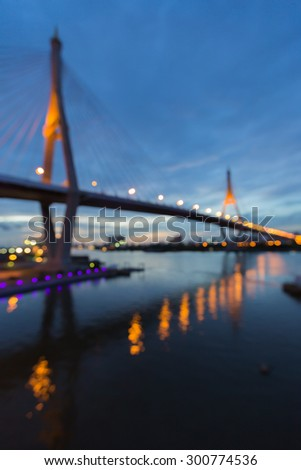 Abstract blurred bokeh lights of Suspension bridge with water reflection #300774536