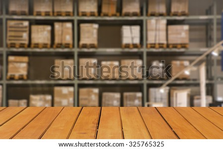 Abstract blurred boxes on rows of shelves in big modern warehouse background