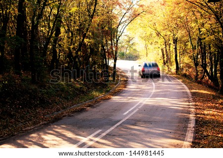 abstract blurred car in autumn forest road