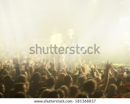 Abstract blurred concept image. Crowd during a musical performance. Hand fans during a concert in fun zone people taking photographs with touch smart phone during entertainment public concert #581368837