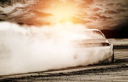 Abstract blurred drift cars with smoke from burned tire at sunset