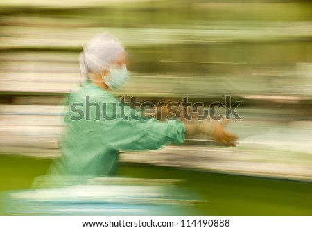 Abstract, blurred figure of nurse runing busy during operation
