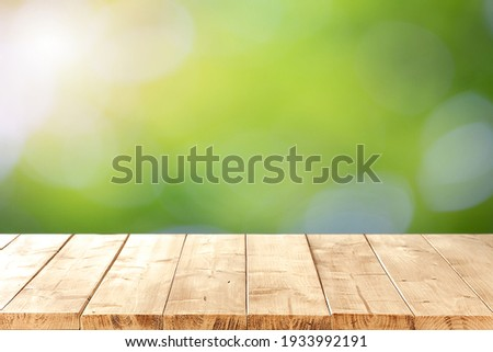Abstract blurred green bokeh and  brown wooden tabletop texture perspective counter for promoting and advertising product on display