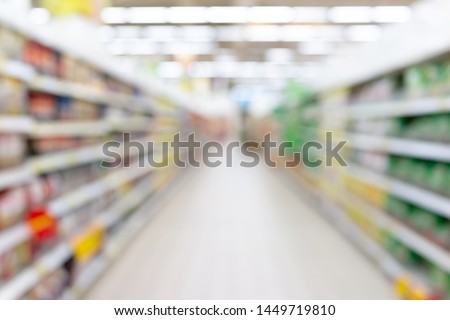 Abstract blurred grocery store aisle with colourful products on display shelves as background. Concept sale clearance in supermarket.
