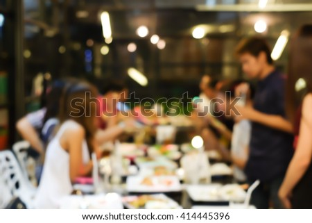 abstract blurred group of asian family meeting in the restaurant background:blurry of caucasian people having funny party after working concept:blur lifestyle manner conceptual.