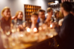 Abstract blurred group of friends meeting in the restaurant. Blurry background of caucasian people having fun, eating and celedrating together. Lifestyle, friendship, party concept