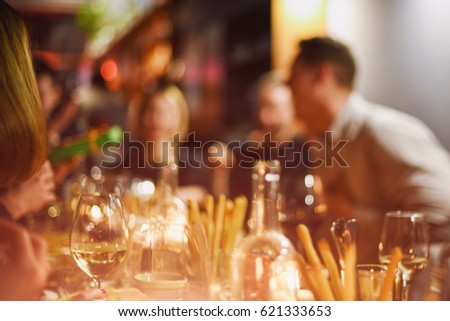 Abstract blurred group of friends meeting in the restaurant. Blurry background of caucasian people having fun, eating and celedrating together. Lifestyle, friendship, party concept #621333653