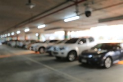 Abstract blurred image background of parking area, ground floor for car parking, Concrete skeleton interior design, Large private garage. shot in the evening with boken light from neon.