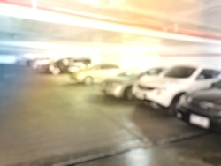 Abstract blurred image of car in parking area at office building.