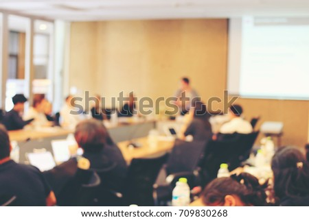 Abstract blurred image of education people and business people sitting in seminar room for profession seminar and the speaker is presenting new technology and idea sharing activity. education concept