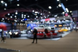 Abstract blurred image of people in cars exhibition show including activities and innovative automotive exhibitions at display. Blurred for background concept.