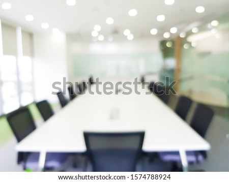 Abstract Blurred large conference meeting room with urban modern office decoration with no people. Professional workplace bright natural light, for wallpaper backdrop or background.