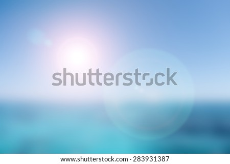 abstract blurred nature background of blue sea and sky with sun light and red flare