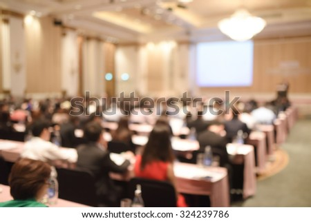 Abstract blurred people in big meeting or conference room for background. Warm tone photo.