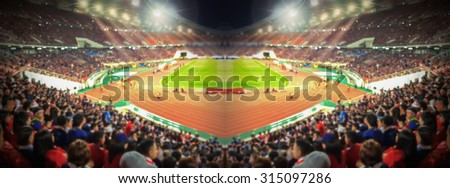 Abstract blurred photo crowd of spectators on a stadium with a football match, sport background concept