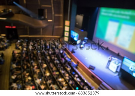 Abstract blurred photo of conference hall or seminar room with attendee background in with low light situation, business and education concept