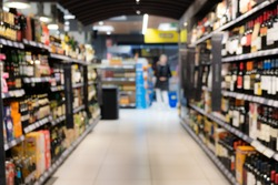 Abstract blurred supermarket aisle with colorful shelves and unrecognizable customers as background