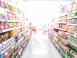 Abstract blurred supermarket aisle with colorful shelves and unrecognizable customers as background.