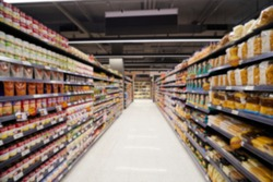 Abstract blurred supermarket aisle with colorful shelves as bokeh background. Unrecognizable customers as background.