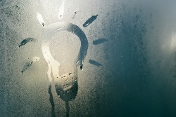 Abstract blurry background of foggy window with light bulb drawing, rainy season.