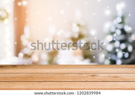 abstract blurry beautiful of decoration Christmas tree in sweet house with snowfall effect background  and plank wooden texture floor for show, advertise, promote product concept