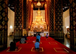 Abstract blurry Buddhist people worship giant golden buddha statues in the Buddhist temple at Ayutthaya Thailand.